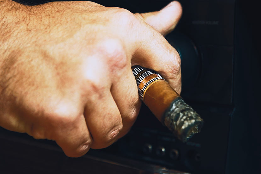 hand with cigar turns up stereo